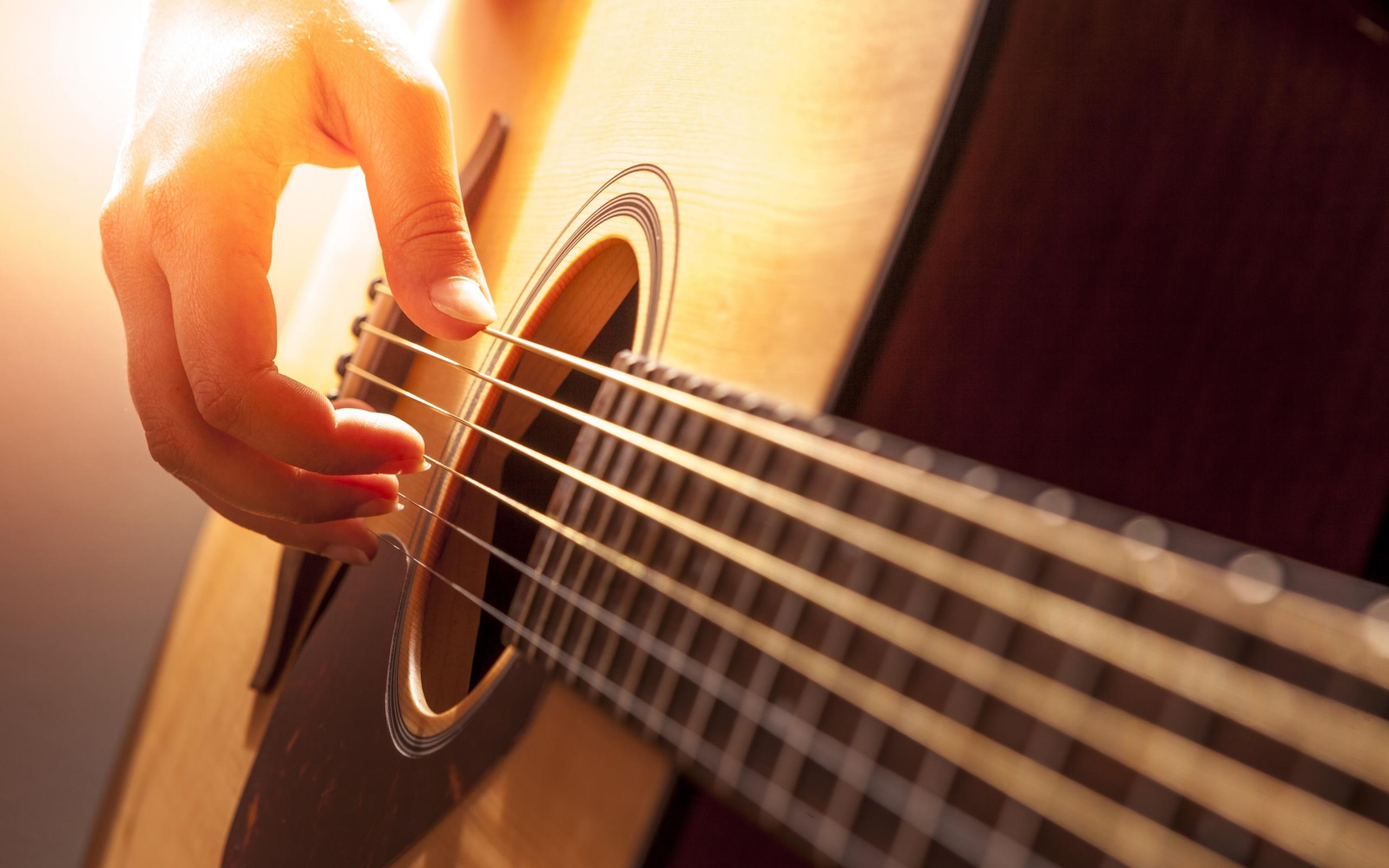 mão tocando violão com luz ao fundo